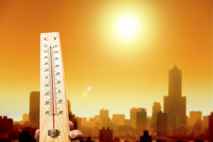 heat wave in the city and hand showing thermometer for high temp